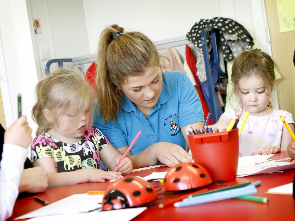 Children and staff member drawing together