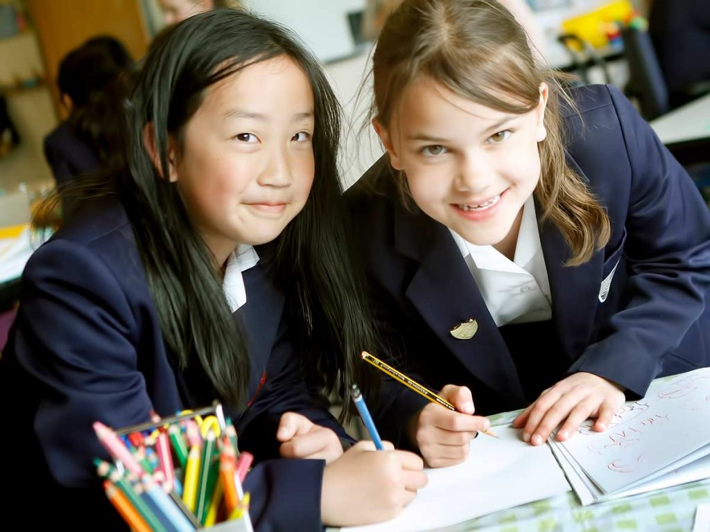Two school children writing together