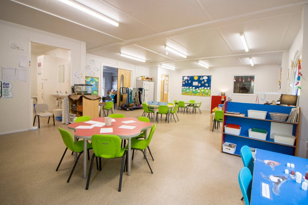 A nursery room filled with coloured chairs and tables