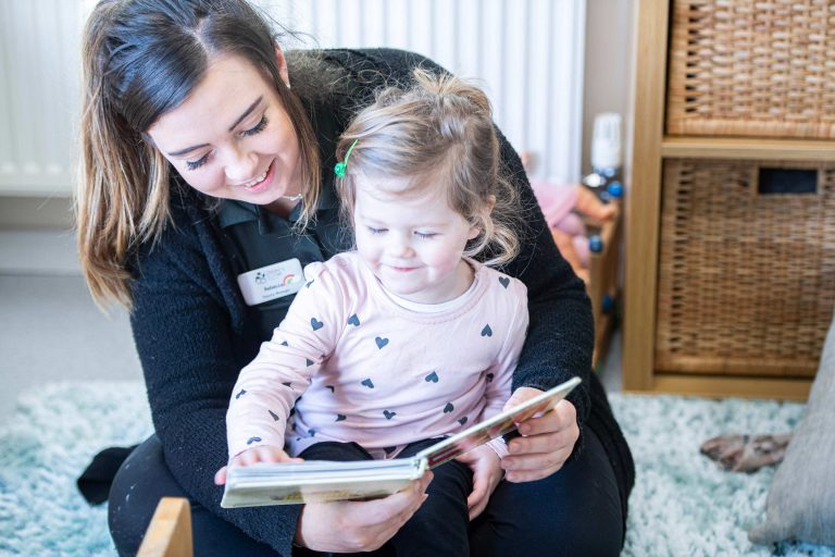 Child reading with a staff member
