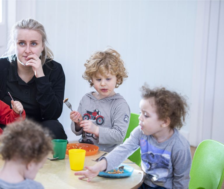 Nursery Practitioner with children at meal times